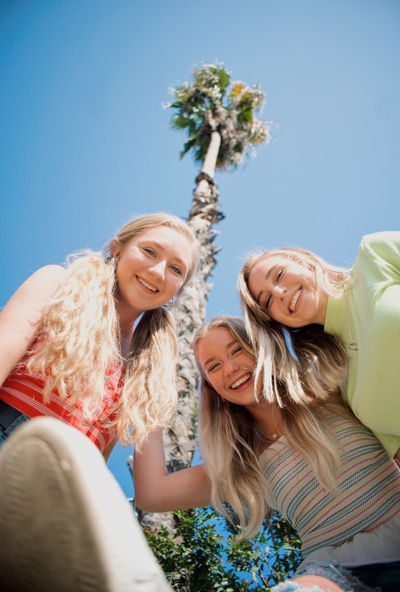 3 women smiling and standing under blue sky during daytime