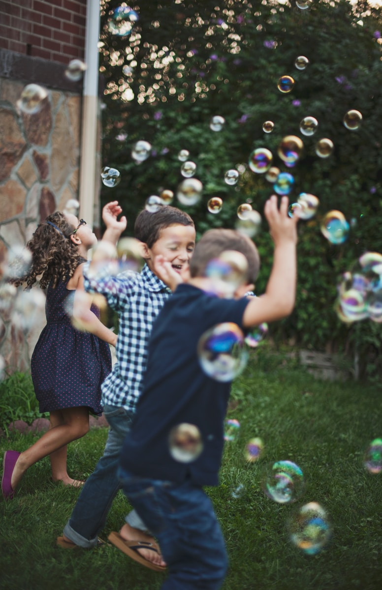 boy in blue and white polka dot shirt playing bubbles